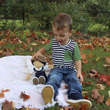 A little boy sitting with his Joe Denim Toddler Boy's Doll