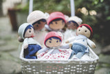 an assortment of Kaloo's my first dolls in a basket