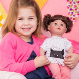 A little girl holding Kitty Kisses Cuddle & Coo interactive crybaby doll by Adora