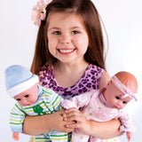 A young girl holding two adora dolls including the baby boy doll