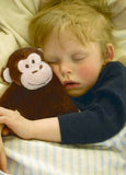 Little boy cuddling children's heating pad stuffed monkey