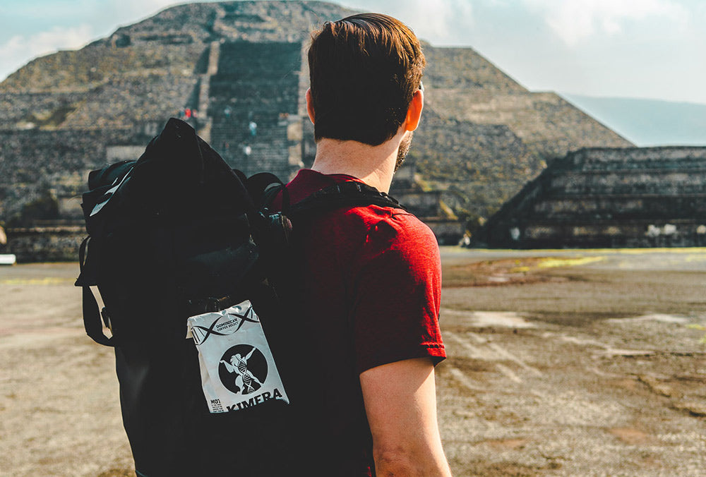 man wearing a backback with a Kimera Koffee bag in one of the pockets lookigaway from the camera at a South or Central American pyramid