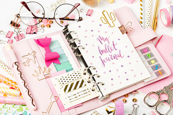 Pink bullet journal on desk
