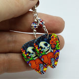 Sugar Skull Surrounded By Flowers Holding a Heart Guitar Pick Earrings with MultiColor Pave Bead