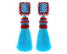 Handmade with colourful turquoise tassels, Isadora earrings by Jolita Jewellery are anchored by a beautiful opal. Sparkling vibrant red crystals outline their playful shape.
