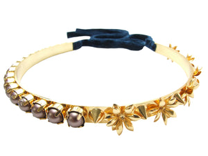 Dipped in gold Jasmine metal choker is embellished with flowers, spikes and velvet brown Swarovski pearls. Fastens at the back with a luxurious velvet ribbon.