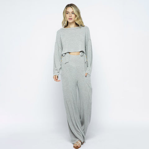 Illa Illa Ribbed Wide Leg Pants/Overalls. These bottoms are the perfect pick for your off-duty wardrobe! Featuring a super comfy ribbed material, high waisted fit, pocket and button detailing, and a wide leg style. Pair this with the matching top and fresh kicks to complete the look.