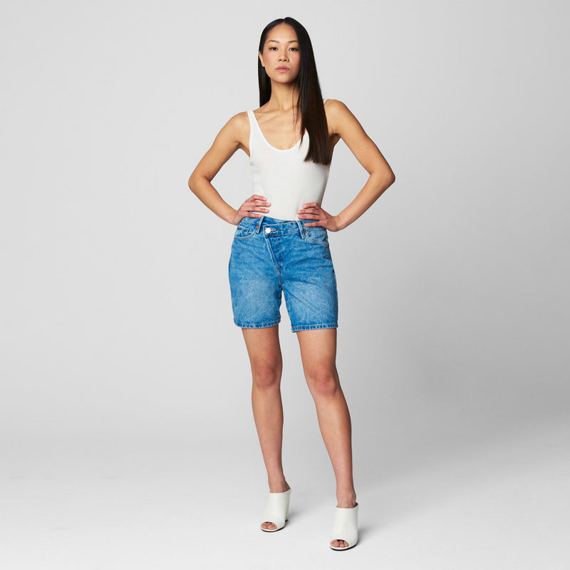 Blank NYC Fare Warning Denim Shorts. Add some edge to your denim short collection with this killer piece! Featuring a medium wash denim colored material, asymmetrical cross-over button detail, and pockets detailing. Pair with a white bodysuit, platform sandals, and crossbody bag for a cute, trendy look!