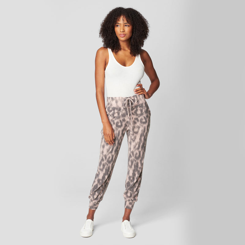 Blank NYC Animal Print Joggers. Perfect for your chill days, these joggers will definitely be your new favorites! Featuring a black and pink leopard print material, high-waisted fit, adjustable jaw-string detail, and a cinched style around the ankle. Pari with the matching sweatshirt and fresh white sneakers.
