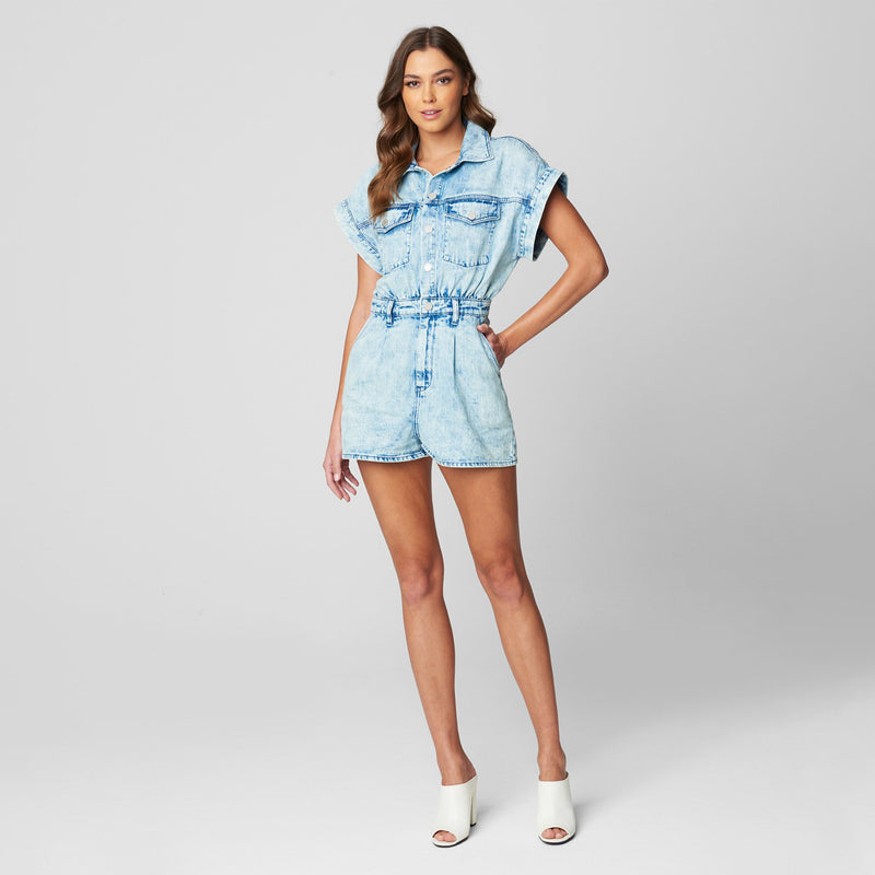 Blank NYC Acid Wash Denim Romper. Absolutely kill all of the trends with our new favorite romper! Featuring an acid wash denim material, short sleeves, button down closure, and pocket detailing. We love this paired with white platform sneakers and tousled waves for the ultimate new-season look.