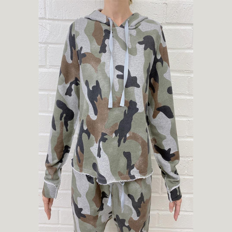 Camo Print Hooded Sweatshirt. Take your lounging look up a notch with this sweatshirt! Featuring a camoflauge printed material, long sleeves, super soft material, hooded detail, and a raw hem trim. Pair with black joggers, crossbody bag, and fun sneakers for a cool off-duty look.