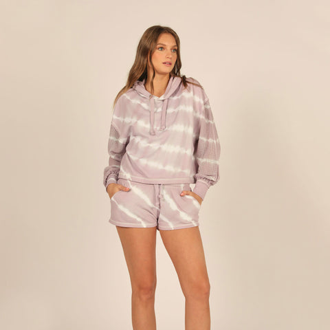 Vintage Havana Tie Dye Mesh Sleeve Elastic Bottom Hoodie. This tie dye hoodie is the ultimate essential for those lounge around! Featuring a lavender and white fabric with a tie-dye print and hoodie detail. Team this hoodie with the matching tie dye bottoms and fresh white kicks for a look that will keep you on point!