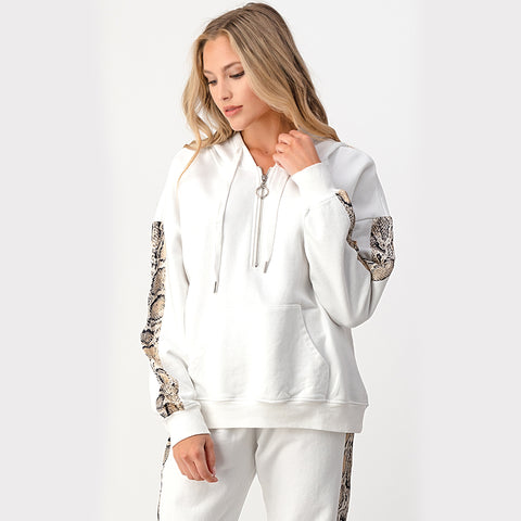 Quarter Zip Snakeskin Hoodie. Feel cozy yet look so trendy with this gorgeous hoodie! Featuring a 1/4 zip hoodie style, a white color material with snakeskin details, and adjustable jaw string. Pair with the matching high waisted snakeskin joggers and slides for a stylish look.