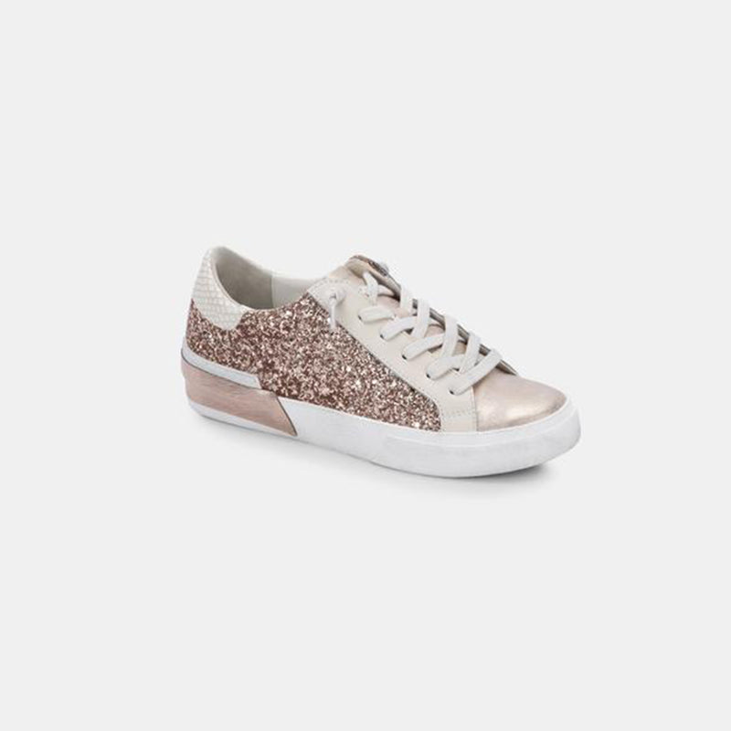 Dolce Vita Zina Sneaker. Obsessed is an understatement! Elevate your sneaker game with these gorgeous kicks. Featuring a white and pink leather material, pink glitter details, and a lace up style. Pair with any fit to instantly elevate it.