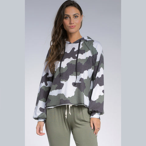 Elan Long Sleeve Camo Hoodie. We are loving everything camo lately, and this hoodie is at the top of our list! Featuring a white, green, and grey camoflauge material, adjustable jaw-string detail, hoodie style, cinched cuffs, long sleeves, and flowy silhouette. Pair this hoodie with joggers and platform sneakers for a trendy, everyday look.