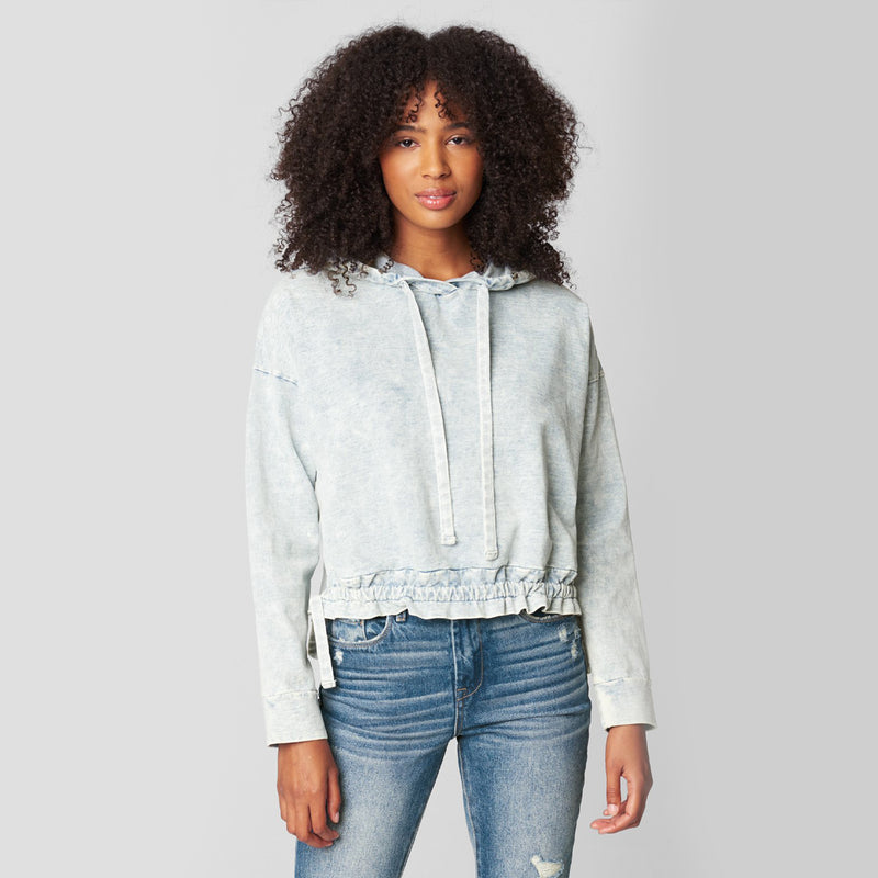 Blank NYC Free Spirit Sweatshirt. Lounge in style with this ultra cute sweatshirt. Featuring long sleeves, adjustable jaw-string detail, ruched trim, and a hoodie detail. Pair with denim or joggers for a trendy, casual look!