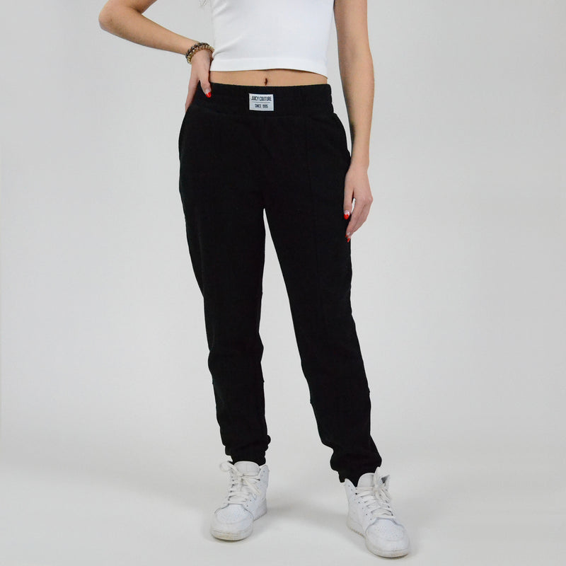 Juicy Couture Pin Tucked Jogger. Perfect for dressing up and down, these joggers are an absolute must-have! Featuring a high waisted fit, front label detail, pin tucked style, and cinched detail at the ankle. Dress up with a bodysuit and heeled ankle booties, or dress it down with a cropped sweatshirt and sneakers.