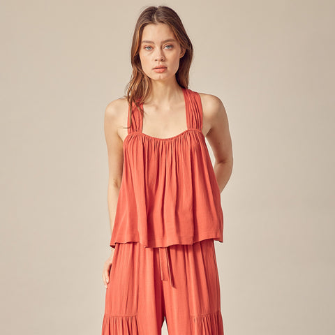 Racer Back Flowy Tank Top. Add a pop of color to your wardrobe with this must-have tank! Featuring a gorgeous burnt orange color, tank top style, racer back style, and a flowy fit. We love this paired with a denim mini skirt, sandals, and your summer glow to finish the look.
