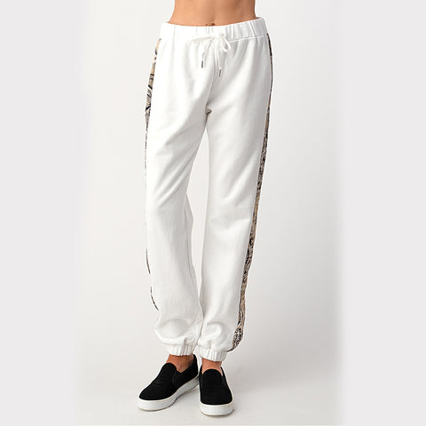 High Waisted Snakeskin Jogger. Add a touch of fun to your loungewear collection with these super cute joggers! Featuring an ultra cozy material, white color with snakeskin details, high waisted fit, adjustable jaw string, and cinched ankle. Pair with the matching hoodie and platform sneakers for a look we are loving!