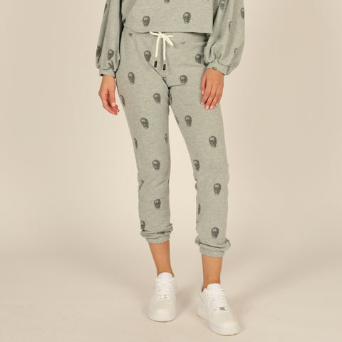 Vintage Havana High Waisted Skull Print Jogger. Take your everyday lounge look to the next level with these bottoms! Featuring a super soft grey material, black skull print design, high waisted fit, adjustable jaw-string detail, and cinched in style at the ankle. Pair with the matching skull printed crewneck and your fave sunnies for a look we are loving!
