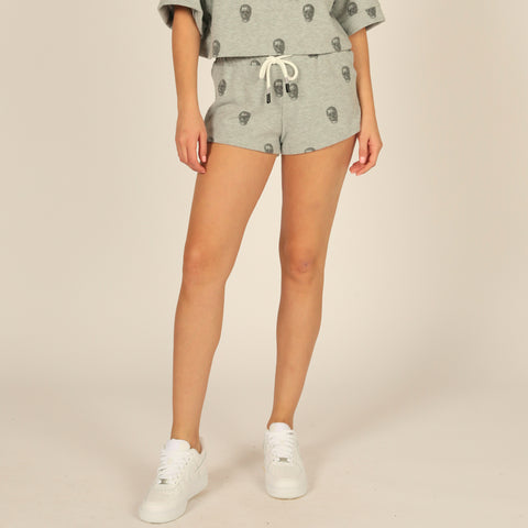 Vintage Havana Skull Printed Shorts. Add edge to your everyday lounge collection with these adorable shorts. Featuring a grey colored material, skull print design, and adjustable jaw string detail. Pair with the matching skull printed crewneck, slides, and a crossbody bag for a super fun look!