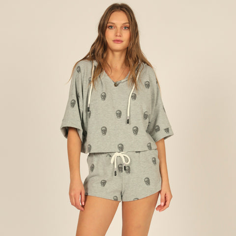 Vintage Havana Short Sleeve Skull Print Hoodie. Look effortlessly cool in this super fun hoodie! Featuring a soft grey material, black skull design, short sleeves, adjustable jaw-string, hoodie detail, and a v-neck style. Pair with the matching skull printed shorts, white sneakers, and a mini backpack for the trendiest look.
