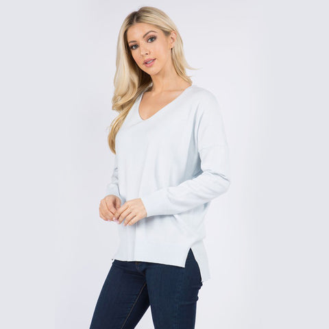 Moonbeam Long Sleeve V-Neck Sweater. We are loving this cute sweater for your new season wardrobe! Featuring a cozy knitted material, v-neck detail, long sleeves, and a fitted style. Tuck this piece into some faux leather shorts, gold accessories, and knee-length boots to complete the look.