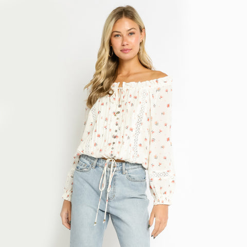 Lily Off The Shoulder Floral Blouse. Look like an absolute dream in our new favorite Springtime top! Featuring a gorgeous floral printed material, off the shoulder style, long sleeve, lace-up details, and a loose fit. Pair with light-wash denim and tousled waves for such a romantic look.