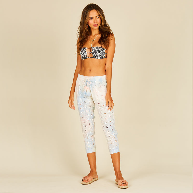 Surf Gypsy Tie Dye Eyelet Genie Pant. Paired with a matching top, or over a bathing suit, these eyelet pants are a versatile vacation essential! Featuring a pastel tie dye printed material, high rise fit, elastic waistband, tie front detail, and a cropped style.