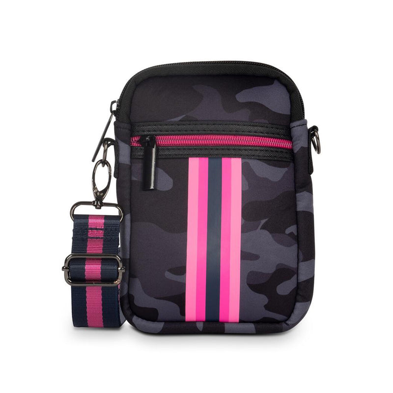 Haute Shore Casey Epic Crossbody Bag. The perfect on the go companion! The Haute Shore Casey Epic Crossbody offers compact construction that accommodates a phone, lipstick and has credit card slots. Featuring a camouflage material with a navy and hot pink stripe detail.