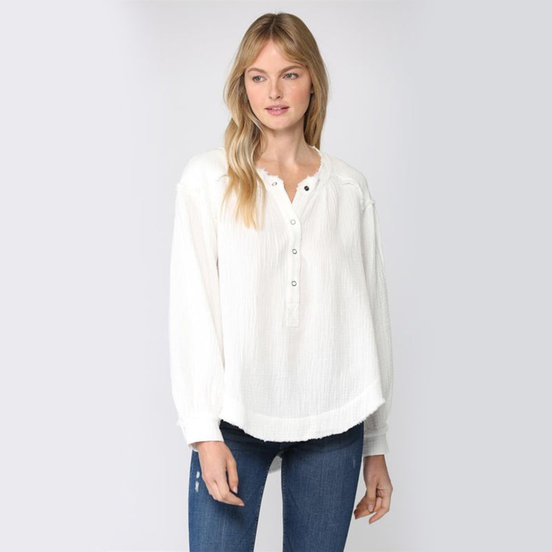 Long Sleeve Button Up Gauze Top. We are loving this top for your new season wardrobe! Featuring a gorgeous cream color material, long oversized sleeves, button closure detail, and a trendy raw hem. Pair with denim and booties for an easy, everyday look.