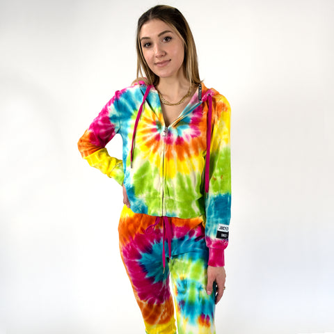 Juicy Couture Long Sleeve Tie Dye Hoodie. Kill the loungewear game in this adorable hoodie. Featuring a multi-colored tie dye material, long sleeves, hoodie detail, zipper closure, and adjustable jawstring detail. Pair with the matching tie-dye joggers, platform sneakers, and beachy waves for the perfect Springtime lounge look.