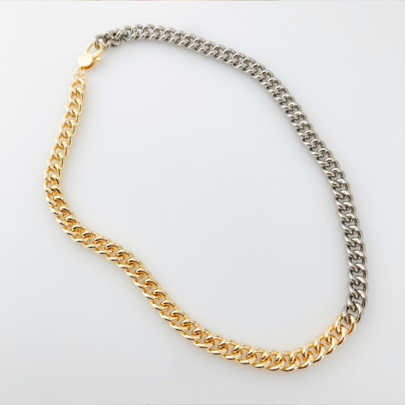 Two Tone Curb Chain Necklace. Steal all the stares with this stunning and trendy piece! Featuring a curb chain style, half silver and half gold color, and a gold lobster clasp. Layer with gold and silver jewelry for a fun mixed look.