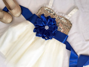 Champagne gold sequin and ivory flower girl dress with royal blue sash.