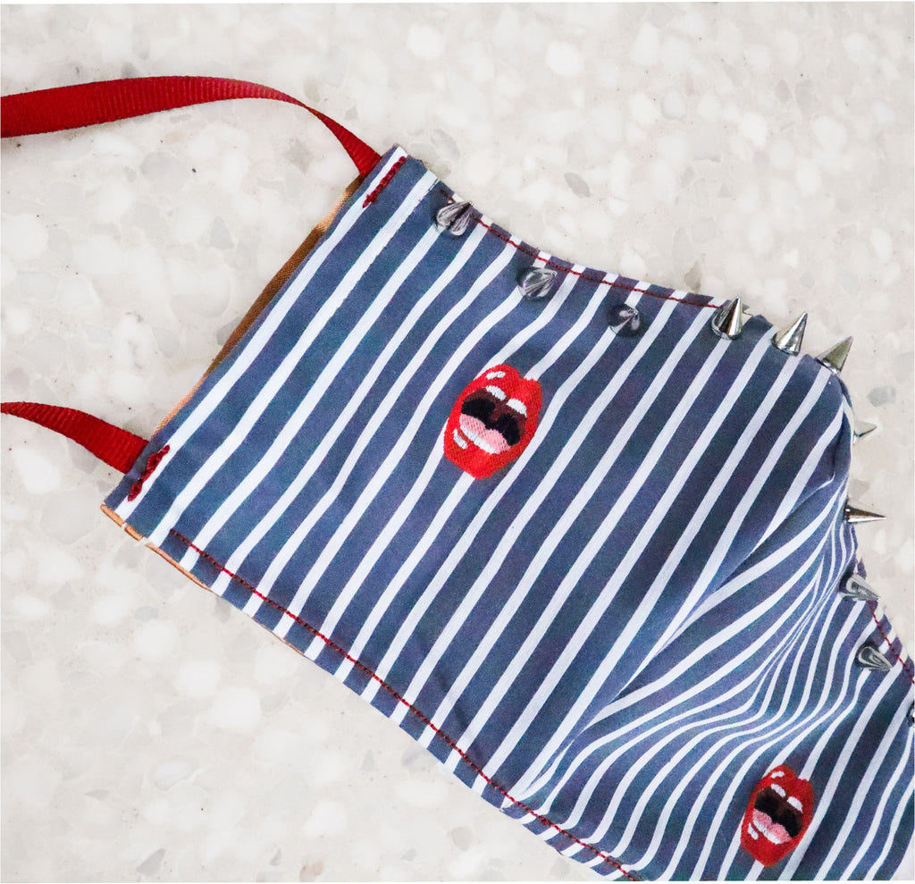 With a sassy lip design, bold pops of red, stripes, AND silver spike detailing, this punk face covering is sure to turn heads. The soft fabric is light and breathable, while the ribbon ties ensure comfortable wear.