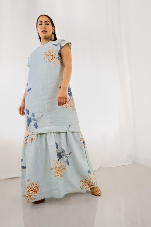 Turn heads in this dusty blue maxi dress. Crafted by hand in Miami using 100% upcycled linen, this piece is simultaneously relaxed and stylish. The floral design is cool and understated, with watercolour blooms in navy as well as pops of orange throughout.  Model fit: XS-SM  100% Upcycled Linen  Handmade in Miami