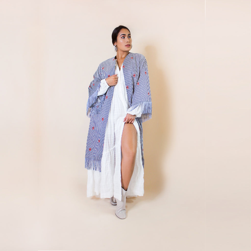 Only One Made. Our lip print kimono looks so good, you'll want to kiss it. Promising to add a playful and stylish touch to any simple outfit, it features an embroidered lip print against a classic stripe background. Finished off with tassels and bell sleeves, it fits and flatters sizes XS - Large.  100% Upcycled Fabric  Handmade in Miami