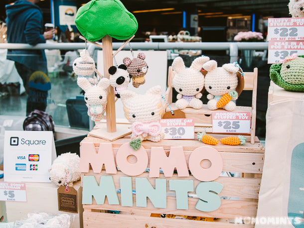 A Wooden Momomints Sign Surrounded by Amigurumi Crochet Stuffed Keychains and Toys