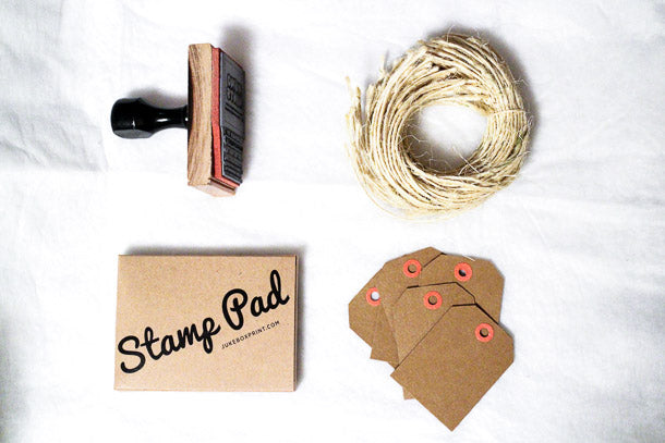 Contents of the JukeBoxPrint.com DIY Custom Stamp Kit - Stamp, Twine, Kraft Hang Tags, Stamp Ink Pad