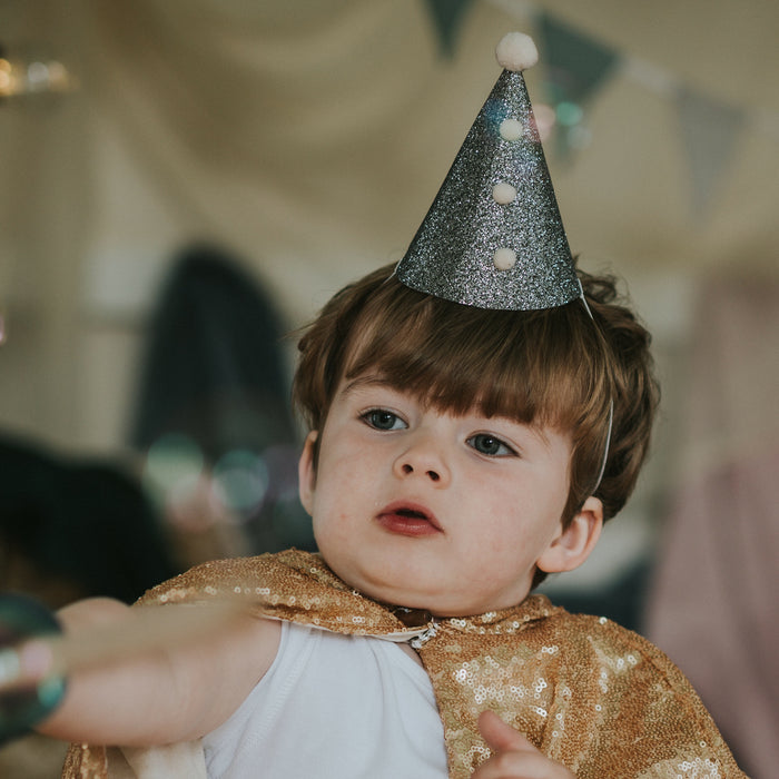 3 year-old boy wearing a Fable Heart Silver Pierrot Party Hat £6 lifestyle image - a handmade dark silver party hat, with four cream Pom Poms.