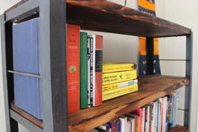 detail shot of Workshop-25 Elements Bookshelf- a 4 shelf bookcase with rustic wood treatment and a steel frame. Shelves are full of books and a decorative wall hanging is in the background.