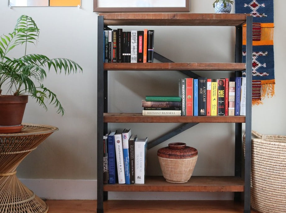 Living room styling of the Workshop-25 Bronzeville Bookcase - Industrial reclaimed wood bookcase with books and objects, 4 shelves, roughly 4.5 feet high, medium width, brown wood, black and gray steel, sturdy design, two crossbars in the back attach like an arrowhead