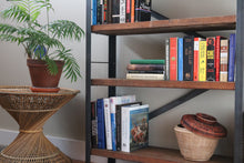 Living room styling of the Workshop-25 Bronzeville Bookcase - Industrial reclaimed wood bookcase with books and objects, 4 shelves, roughly 4.5 feet high, medium width, brown wood, black and gray steel, sturdy design, basket detail, two crossbars in the back attach like an arrowhead