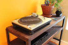 Living room styling of Workshop-25 Roscoe Record Player Table - Industrial reclaimed wood shelf with record player, amp, records, houseplants, 3 shelves, roughly 4 feet high, medium width, dark brown mahogany stained wood, black and gray steel, sturdy design