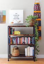 four shelf medium height bookshelf made of rustic wood shelves and steel frame, living room scene with woven art, plant, books, and basket on the bookcase
