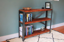 reclaimed wood bookcase by workshop25 with a honey colored stain on the wood, steel frame, bookcase shown with a white Moroccan rug against a teal wall - bedroom styling with books, basket, vase, and a plant