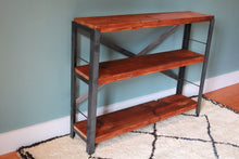 reclaimed wood bookcase by workshop25 with a honey colored stain on the wood, steel frame, bookcase shown with a white Moroccan rug against a teal wall - empty shelves to highlight wood character