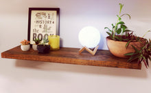 floating shelf on light blue wall - reclaimed wood in a medium brown color - shelf is styled with 1 medium plant in a terracotta pot, a lightup led moon lamp , 1 candle, 2 small plants and one framed piece of printed art work
