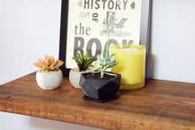 floating shelf on light blue wall - reclaimed wood in a medium brown color - shelf is styled with 1 medium plant in a terracotta pot, 4 books, 1 candle, 2 small plants and one framed piece of printed art work