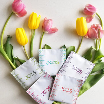 All five JOOS blend packets on top of three yellow tulips and four yellow tulips.